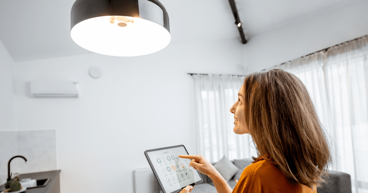 Image of a woman dimming her lights via an app on her tablet